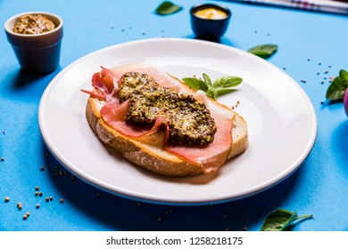 Sandwich with ham and mustard on a white ceramic plate, blue backgrounds with ingredients