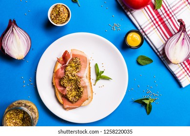 Sandwich with ham and mustard on a white ceramic plate, blue backgrounds with ingredients, top view