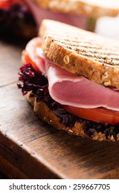 Sandwich with ham, salad, tomato on wooden table