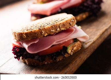 Sandwich with ham, salad, tomato on wooden cutting board