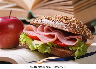 sandwich with ham and vegetables and red apple on open notebook close-up. horizontal