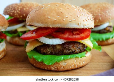 Sandwich homemade hamburger with juicy burgers, cheese,  fresh vegetables