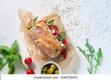 Sandwich with jamon, cheese, tomatoes and arugula on a white background. top view - Shutterstock ID 1564733473