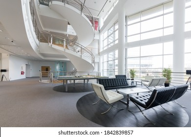 Sandwich, Kent / UK - Oct 28 2020: Modern office building, formerly the home of Pfizer, pharmaceutical company. Image shows stylish reception area, high ceilings, modern furniture and big windows.