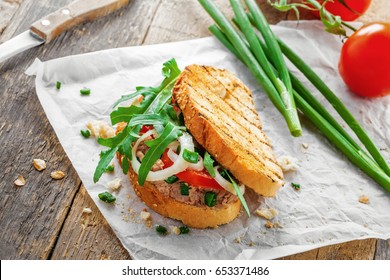 Sandwich made of grilled toasts, tuna salad, tomato, onion and arugula on a table. Delicious healthy meal for lunch.