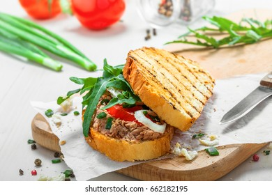 Sandwich made of grilled toasts, tuna salad, tomato, onion and arugula on a white wooden table. Delicious healthy meal with ingredients.