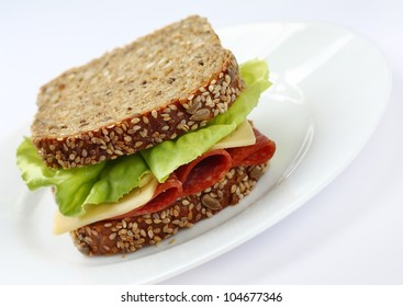 Sandwich made of healthy brown bread with seeds  lettuce italian salami and cheese