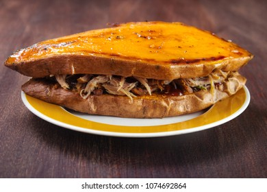 Sandwich made of two owen roasted sweet potato slices and pulled pork with sauce on plate