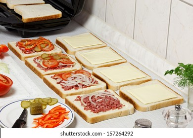 Sandwich maker, toasts and vegetables on the table.
