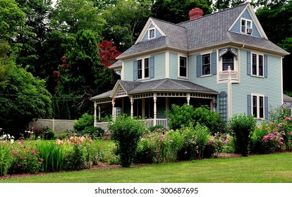 Sandwich, Massachusetts - July 15, 2015:  Victorian-era home with large front porch, gables, and Summer flower garden