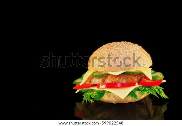 Sandwich with meat, cheese and vegetables on black background