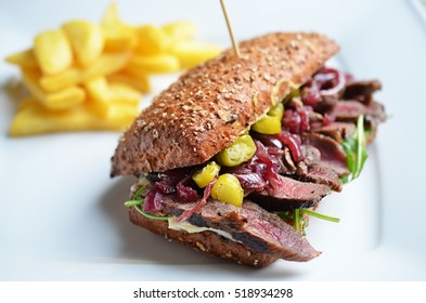 Sandwich with meat onion and hot peppers on white plate.