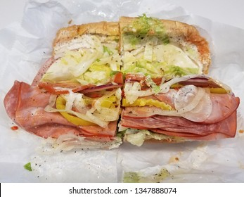 sandwich with meat, peppers, lettuce, and bread