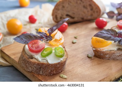 Sandwich with mild creamy cheese and vegetables on cutting board