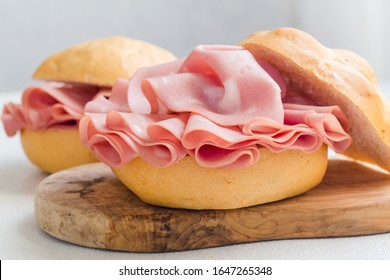 Sandwich with mortadella. Sliced mortadella from Bologna - a large italian sausage or luncheon with meat. Tipycal italian bread - La Rosetta.