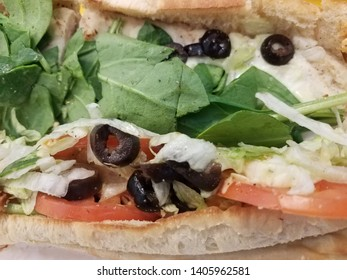 sandwich with olives, tomato, spinach, and lettuce