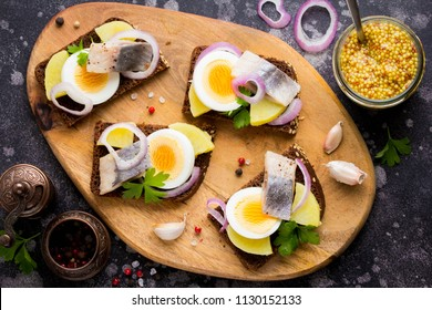 Sandwich on bread with herring, potatoes, egg, onion, tasty appetizer with mustard on the Board