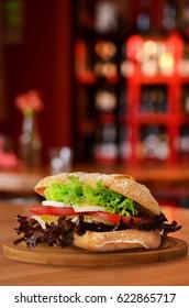 Sandwich on wooden table in restaurant.