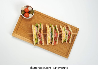 Sandwich on a wooden tray. The sandwich is cut into four pieces and strung on a wooden skewer. Next to a plate of pickles-marinated onions, tomato, cucumbers. White background. View from above.