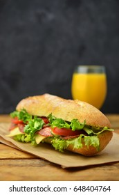 Sandwich and orange juice on wooden table.