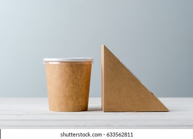 Sandwich paper box and take-out coffee cup, close-up. Light grey background, wooden surface. Busy lifestyle, eating at office.