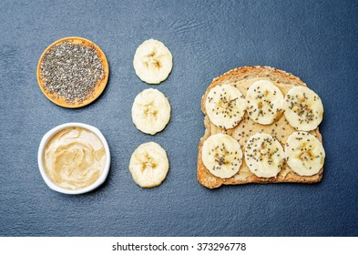 Sandwich with peanut butter, banana and Chia seeds on a black background. toning. selective focus
