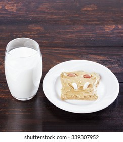 Sandwich with peanut butter on a white plate, glass of milk on a wooden table.