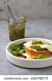 sandwich with pesto, egg in a white plate on a gray concrete background