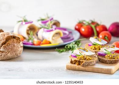 Sandwich with pieces of marinated herring with red onion and french mustard, decorated lemon and rosemary. Close up, restaurant serving, light gray wooden surface, copy space.