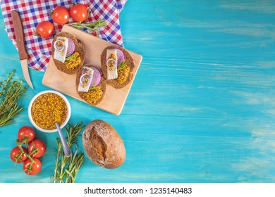 Sandwich with pieces of marinated herring with red onion and french mustard, decorated lemon and rosemary. Close up, restaurant serving, turquoise wooden surface, copy space, top view.