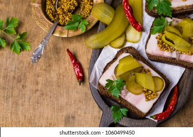 Sandwich with pork fat and pickled cucumbers on wooden background. Selective focus.