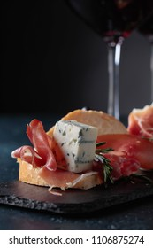 Sandwich with prosciutto, blue cheese and rosemary on a dark background. Delicious snack and glasses of red wine. Copy space for your text.