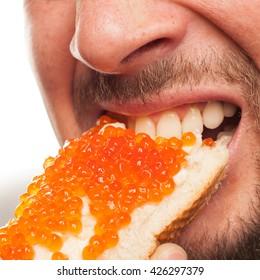 Sandwich with red caviar. Enjoy the food. A man bites a big sandwich with red caviar on a white background.