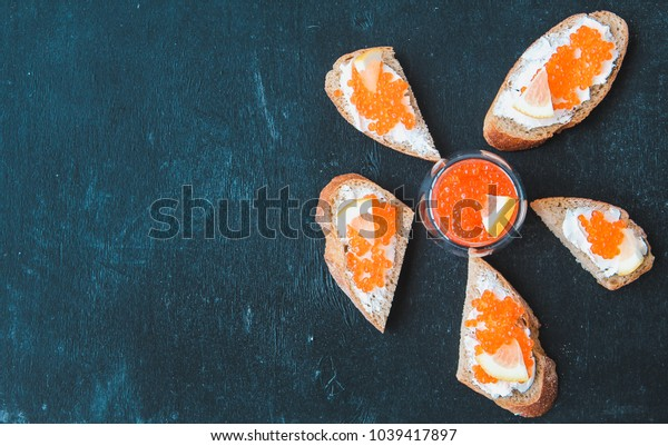 a sandwich with red caviar on a black background