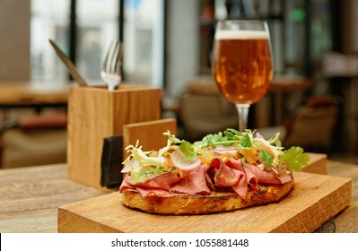 Sandwich with roast beef pastrami on restaurant table, toned image, gold reflector effect