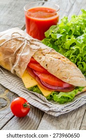 Sandwich with salad, cheese, ham, tomatoes, red onion, juice, ingredients, rustic wood background, top view