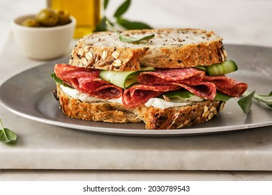 Sandwich with salami sausage and cucumber on marble background.
