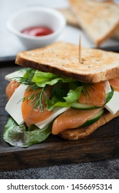Sandwich with salmon, cheese, salad leaves and cucumber, selective focus, closeup, vertical shot