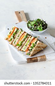 Sandwich with salmon, cucumber and microgreens with wholewheat bread, served on marble board