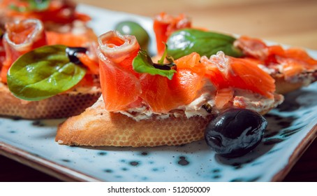 Sandwich with salmon and olives on a plate