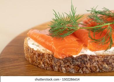 Sandwich with salmon on wooden board