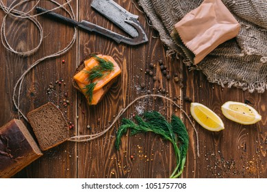 Sandwich with salmon, spices and lemon on a wooden table
