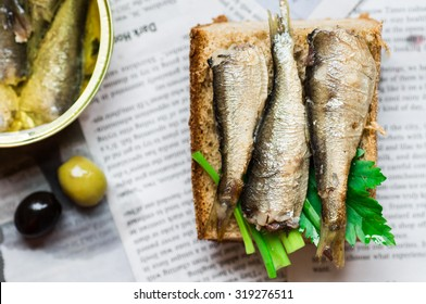 Sandwich with sardine on newspaper top view