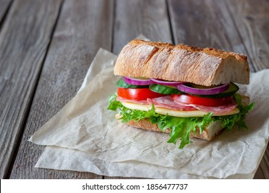 Sandwich with sausage, cheese, green salad, tomatoes, cucumbers and onions. Fast food. Breakfast. Healthy eating