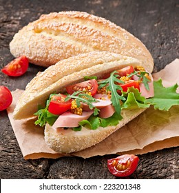 Sandwich with sausage, lettuce, tomato and arugula on the old wooden background