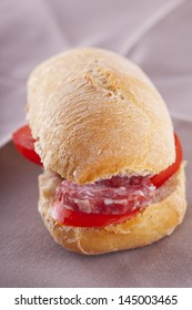 A sandwich with sausage and tomato over brown napkin