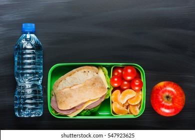 Sandwich, small tomatoes, tangerine, apple in plastic lunch box and bottle of water on black chalkboard.