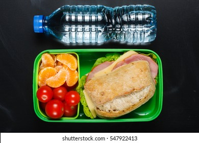 Sandwich, small tomatoes, tangerine in plastic lunch box and bottle of water on black chalkboard.