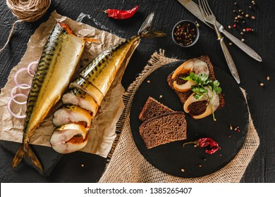 Sandwich with smoked mackerel fish with spices on dark stone background. Smoked fish, mediterranean food, herring fish, seafood, top view