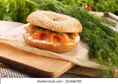 Sandwich with smoked salmon and dill on a chopping board